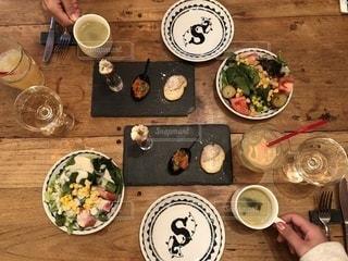 食品のプレートをテーブルに座っている人々の写真・画像素材[1040424]