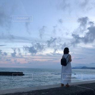 水域の隣に立っている女の写真・画像素材[2408942]