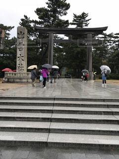 傘を持って雨の中歩く人々 のグループの写真・画像素材[1034030]