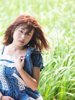 草の前で髪をなびかせる女性の写真・画像素材[1158012]