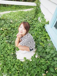 庭に座っている女の子草に囲まれている女性の写真・画像素材[1158016]