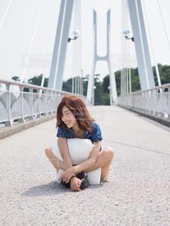 橋の上で枕を持って座っている女の子の写真・画像素材[1279142]
