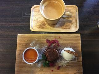 食品や木製のテーブルの上のコーヒー カップのプレートの写真・画像素材[1048016]
