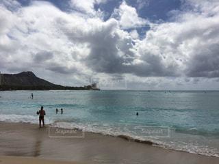 水の体の近くのビーチの人々 のグループの写真・画像素材[1035945]