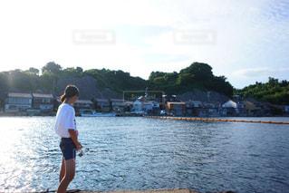 水の体の横に立っている人の写真・画像素材[1402840]