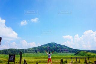 フィールドの背景の山と人々 のグループの写真・画像素材[1038505]