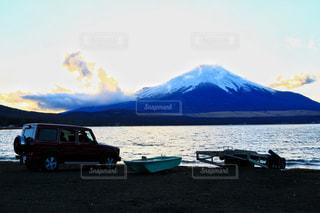 背景の山と水の体のボートの写真・画像素材[1038273]