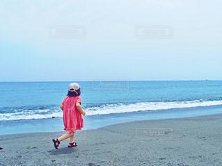 ビーチの上を歩く少女の写真・画像素材[1217933]