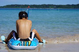 水の体の近くのビーチに座っている人の写真・画像素材[1456473]