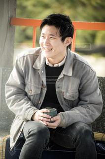 携帯電話で話しているベンチに座っている男の写真・画像素材[1057625]