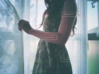 窓の前に立っている女性の写真・画像素材[2210859]