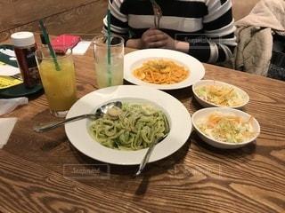 食品のプレートをテーブルに着席した人 - No.1043558