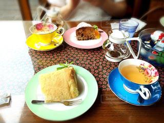 食品やコーヒー テーブルの上のカップのプレート - No.1044051