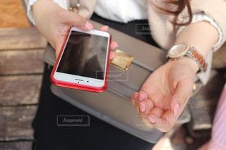 携帯電話を使用してテーブルに座っている女性の写真・画像素材[1084661]