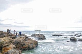 海の近くの岩の上の人々 のグループの写真・画像素材[1048581]