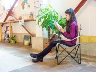カフェの椅子に座って読書をしている女性の写真・画像素材[2505407]