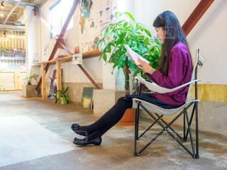 カフェの椅子に座って読書をしている女性の写真・画像素材[2505408]