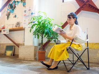 カフェの椅子に座って読書をする女性の写真・画像素材[2506199]