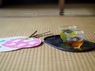 畳の上にある麦茶とうちわの写真・画像素材[3553846]