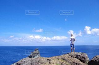 岩のビーチに立っている人の写真・画像素材[1386779]