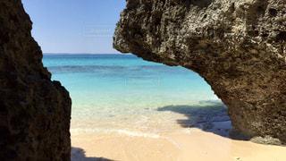 水の体の横にある岩のビーチの写真・画像素材[1387192]