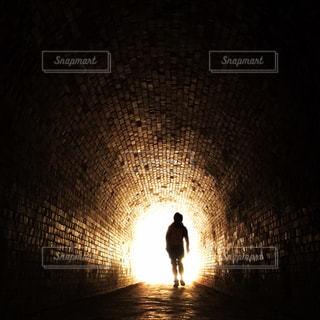 光の道の中に立っている男の人の写真・画像素材[1053224]