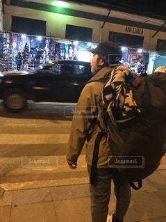 荷物の袋の横の道を歩いている人 - No.1053368