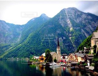 背景の山と水の体中の小型船の写真・画像素材[1053171]