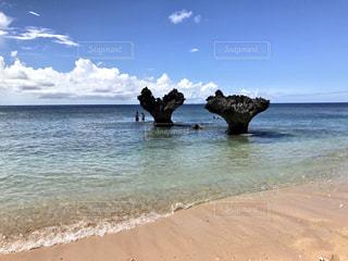 水の体の近くのビーチに立っている人の写真・画像素材[1112657]