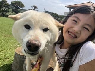 カメラに向かってポーズをとる犬を持っている人の写真・画像素材[2331771]