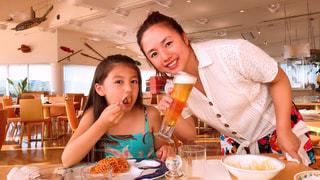食べ物を食べるテーブルに座っている人の写真・画像素材[2387631]