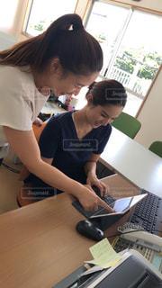 ラップトップコンピュータを使ってテーブルに座っている人の写真・画像素材[2436536]