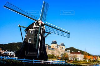 バック グラウンドで市と水の体の横に風車の写真・画像素材[1111729]