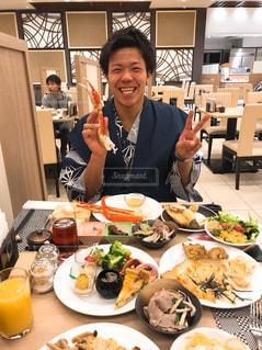 食品のプレートをテーブルに着席した人の写真・画像素材[1063208]