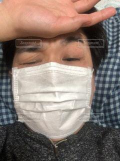 マスクをつけて頭を押さえ顔をしかめている人の写真・画像素材[1064391]