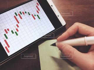 チャートを見ながらメモを取る、投資をする人の写真・画像素材[1072771]