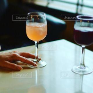 ワインを飲みながらテーブルに座っている人の写真・画像素材[2258940]