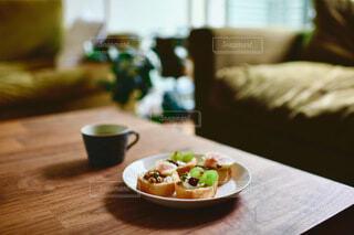 木製のテーブルの上に座っている食べ物の皿の写真・画像素材[3720047]