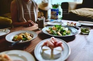 食べ物の皿を持ったテーブルに座っている人の写真・画像素材[3720045]