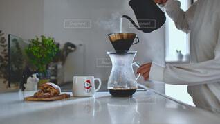 テーブルの上でコーヒーを一杯持っている男の写真・画像素材[4321102]