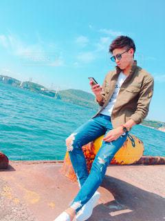 水に携帯電話で話す人の写真・画像素材[1076376]