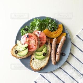 テーブルの上に食べ物のプレートの写真・画像素材[1071536]