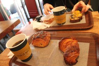 朝食のサンドイッチとコーヒー テーブルの上のカップの写真・画像素材[1170853]