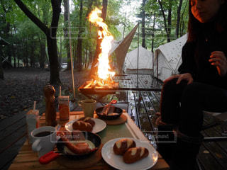 燃えている食品のプレートの前に立っている人の写真・画像素材[1170862]