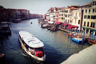 バック グラウンドで市と水の体中の小型船の写真・画像素材[1264407]