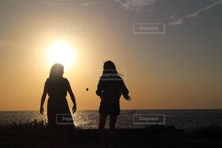 バック グラウンドで夕焼けのビーチに立っている人の写真・画像素材[1272639]