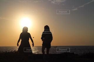 バック グラウンドで夕焼けのビーチに立っている人の写真・画像素材[1272649]