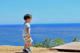 水の体の横に立っている人の写真・画像素材[1312676]