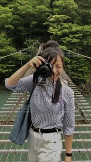 フェンスの横に立っている人の写真・画像素材[1381659]