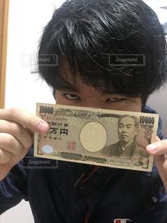 携帯電話を保持している福沢諭吉の写真・画像素材[1077083]